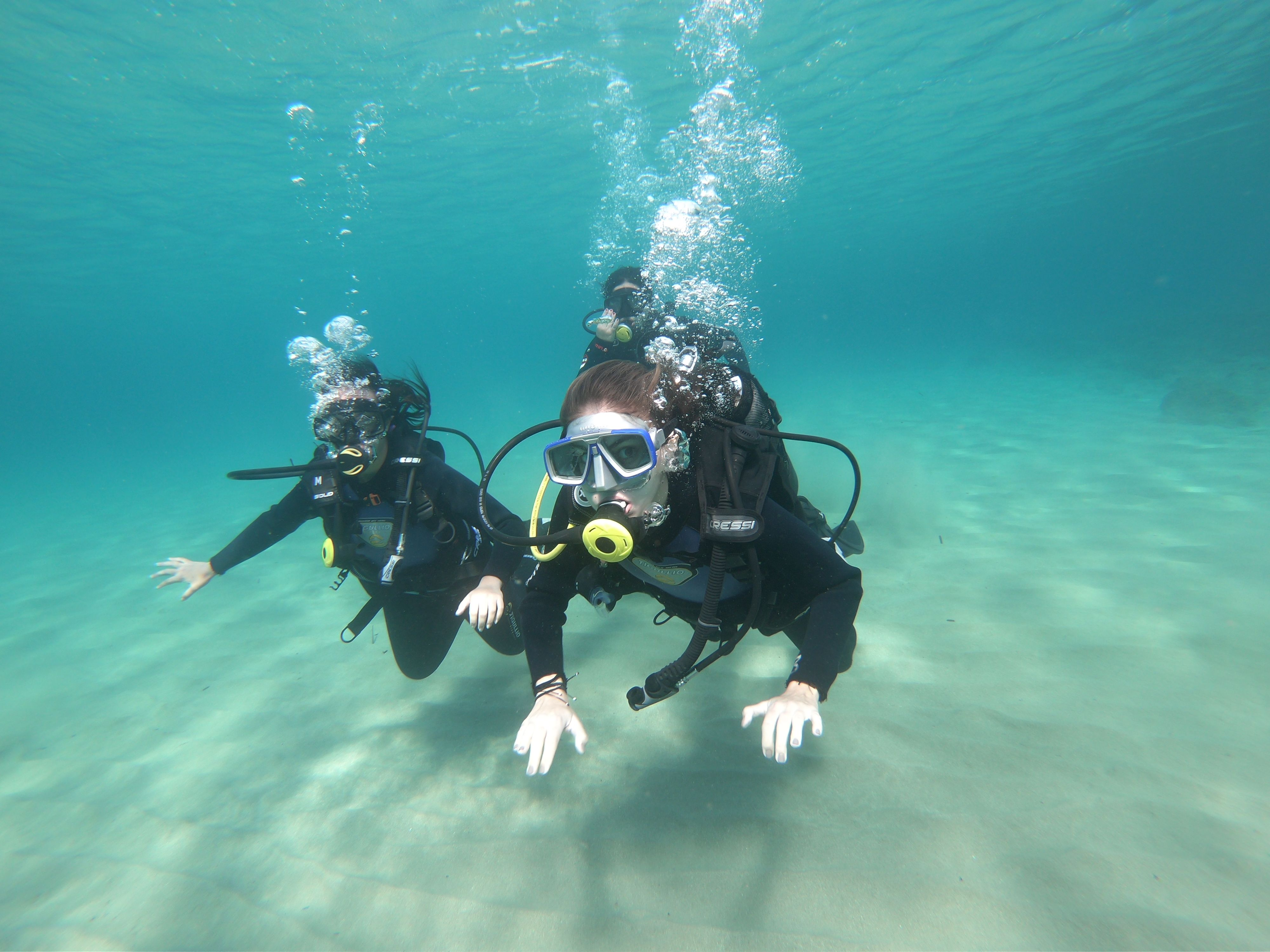 Two women scuba diving in blue waters just above the sandy sea bed