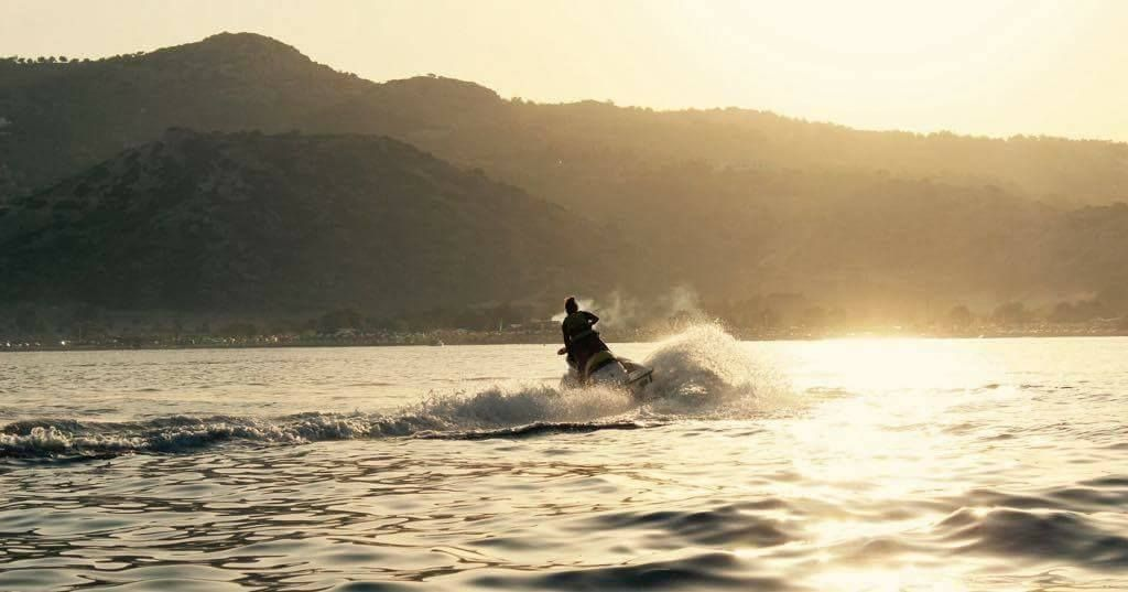 Person jetskiing as the sun sets in Rhodes