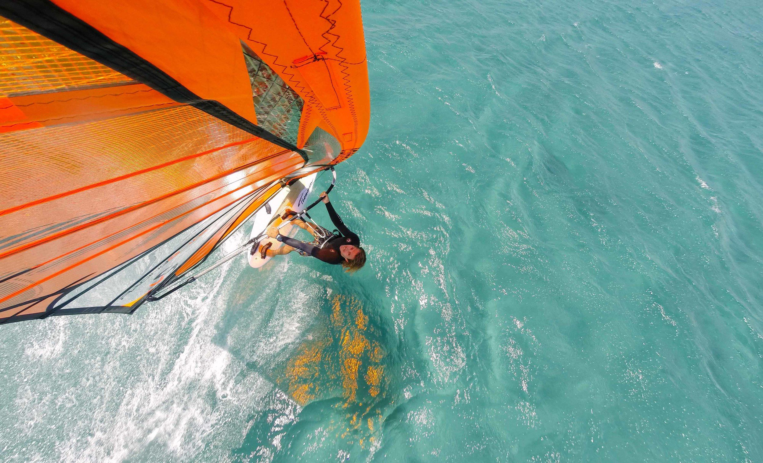 Man windsurfing looking up at camera at top of sail in Schinias Athens Greece