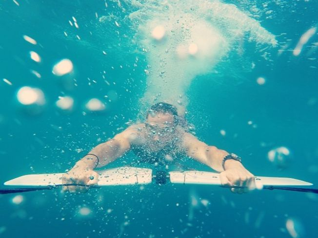 Underwater photo of man riding a subwing in Schinias Athens Greece