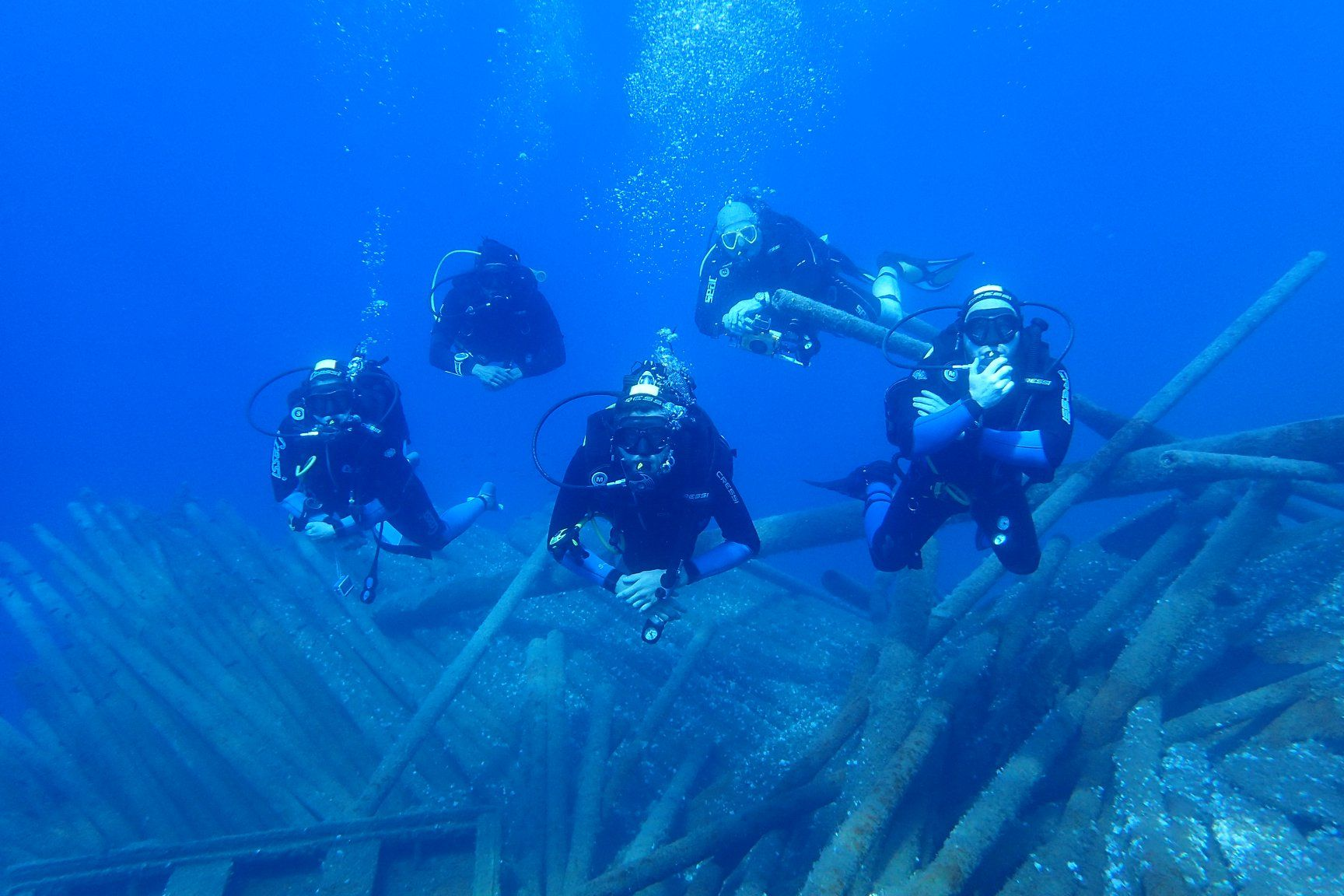 Five scuba divers in extremely blue water over collapsed pipes