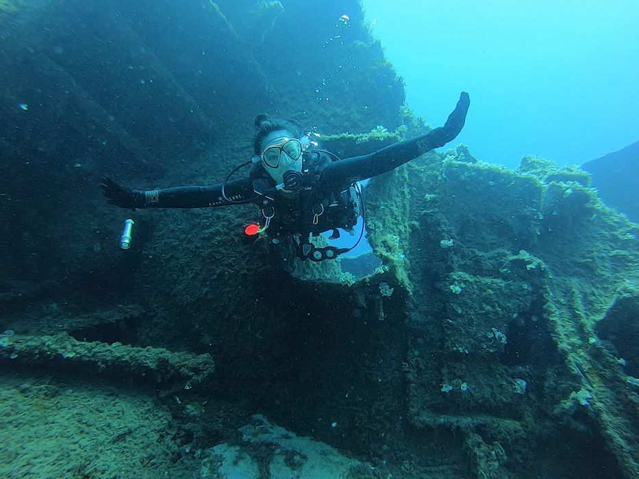 A female diver swimming through a whole in a shipwreck