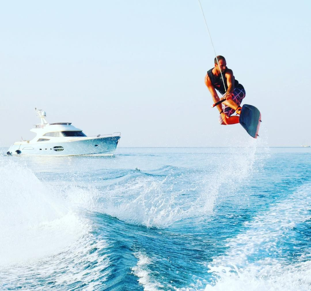 Wakeboarder getting air with yacht in background