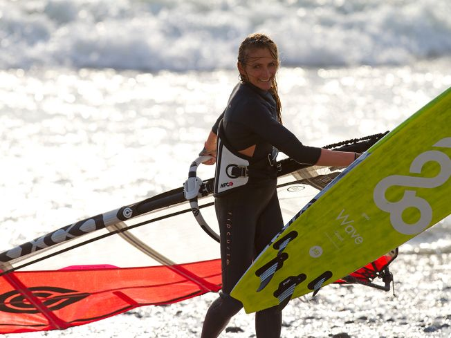 Tony Frey carrying Goya windsurf board out of sea