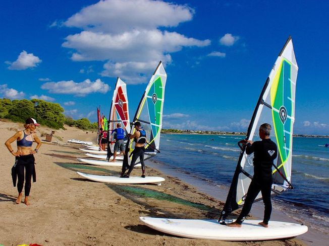 People being shown how to windsurf on beach
