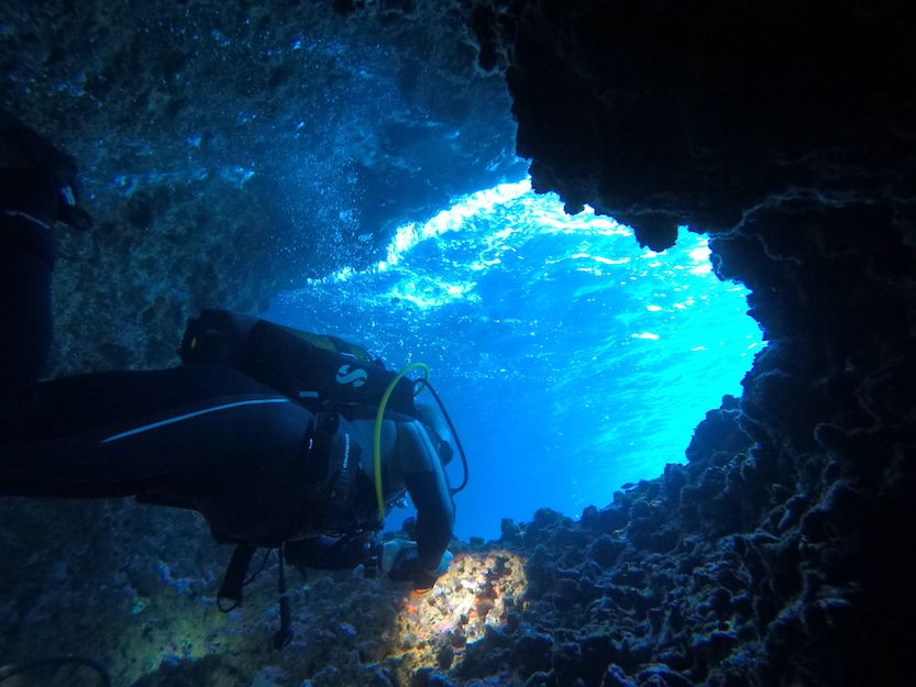 Scuba diver swmming through cave in Evia