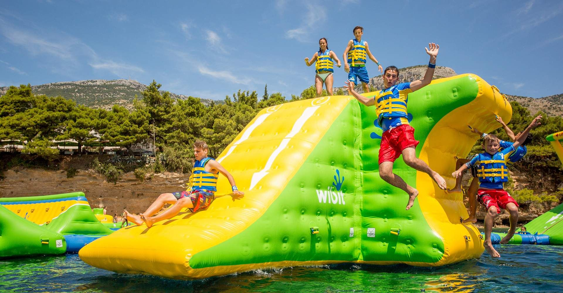 Boys jumping off inflatable tower in to the sea