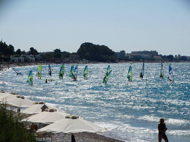 Lots of people windsurfing in Rhodes with the sun reflecting off the sea
