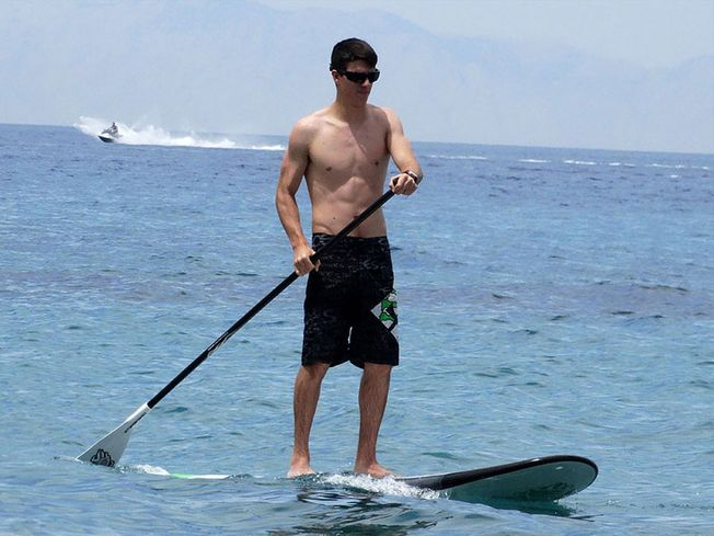 Man on a Stand Up Paddle with jetski in background