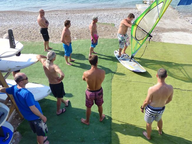 Group being shown how to windsurf on test board on land