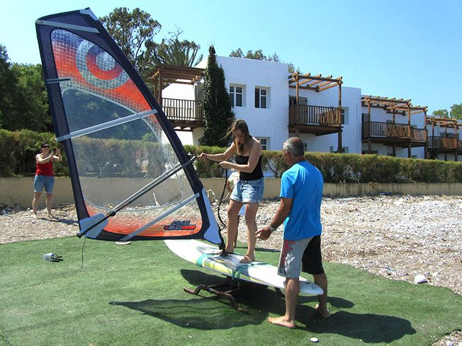 Woman being shown how to pull up windsurf sail on test windsurf board on land