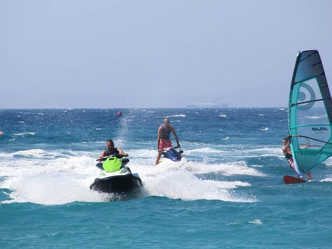 Two men on jetskis and a windsurfer