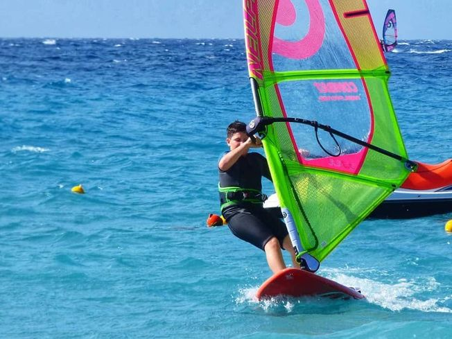Young boy windsurfing in blue sea