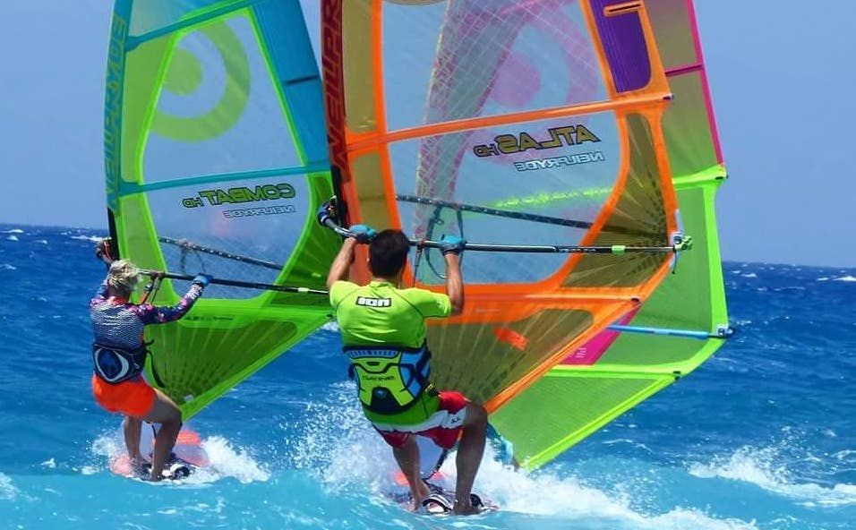 Man and woman windsurfing with brightly coloured sails in the blue waters of Rhodes