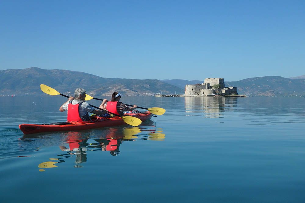 Two people kayaking in still nafplio sea towards castle in greece