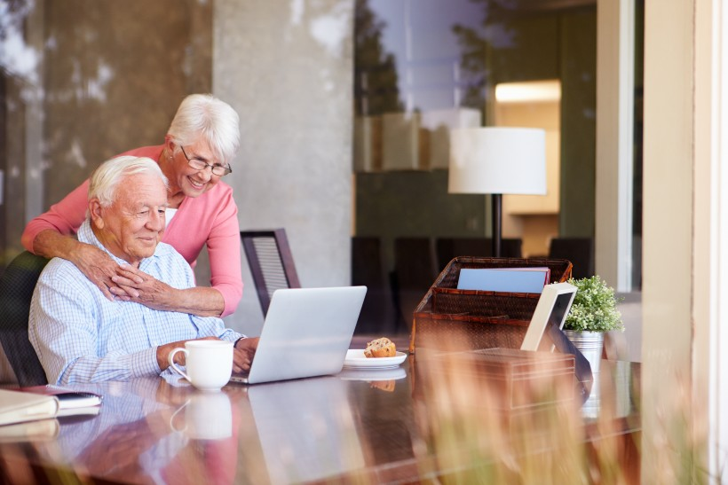 elderly couple video chatting loved ones on their laptop