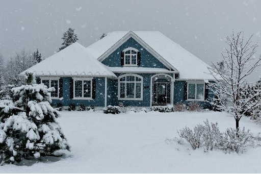 dark blue house covered in lots of snow as the snow continues to fall