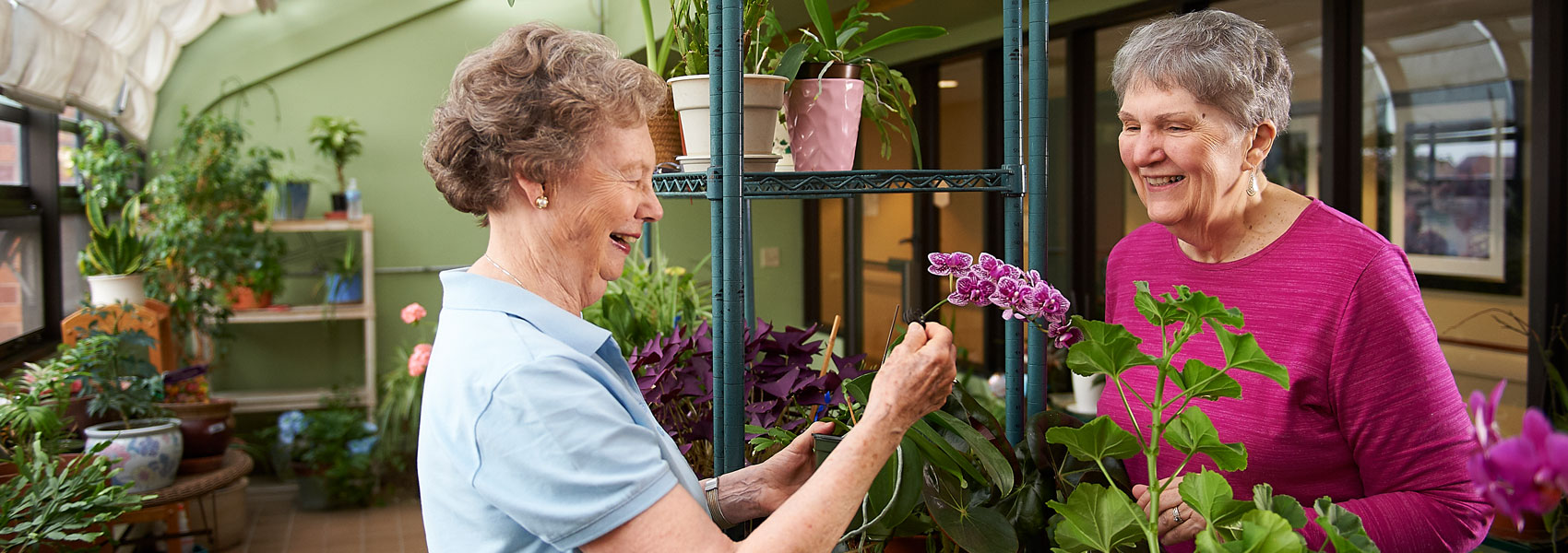 Two elderly women looking at plants in the greenhouse at Beacon Hill retirement community