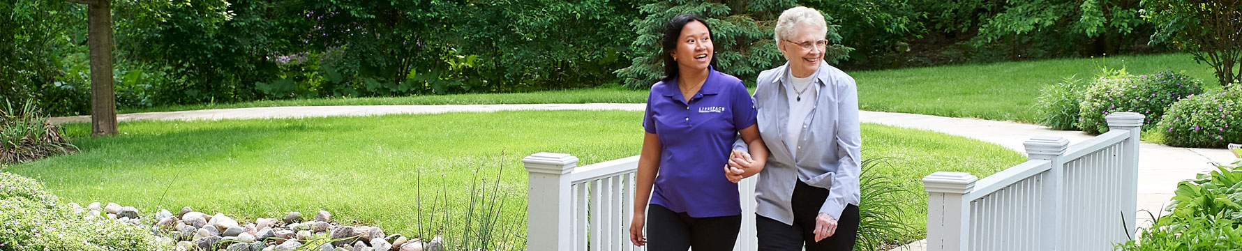 an elderly women walking across a bridge with her caregiver
