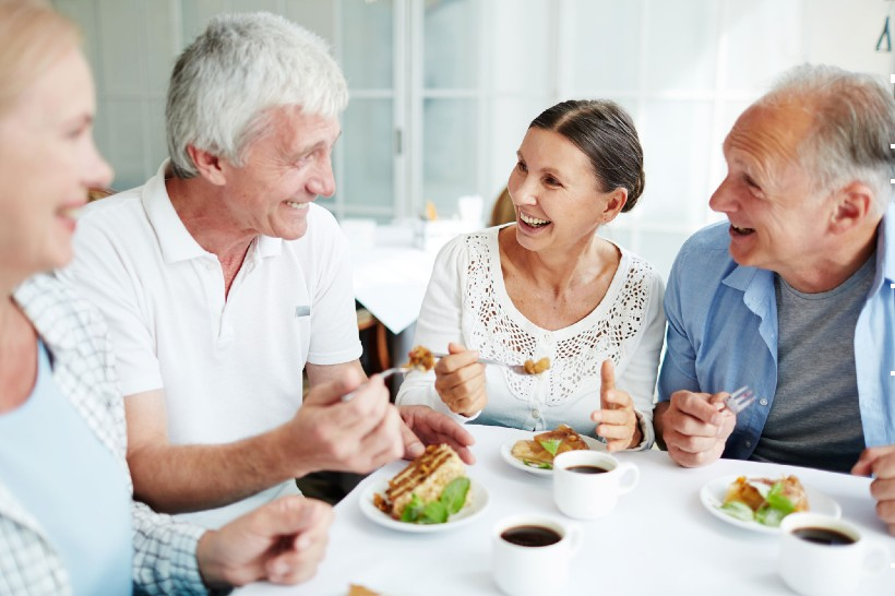 group of seniors enjoying a meal together in their senior living community