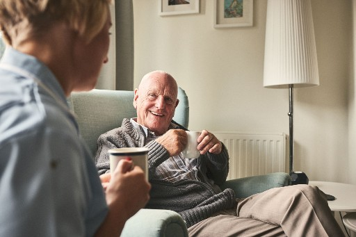 elderly man having a cup of coffee with a nurse in a retirement home