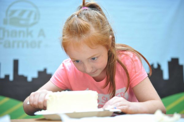 A young Fairgoer partakes in a butter sculpting contest in the Paul R. Knapp Animal Learning Center.