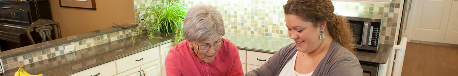 A senior living staff member helps an elderly woman in her kitchen