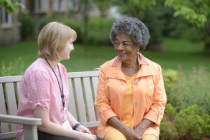 Senior and caregiver sitting outside