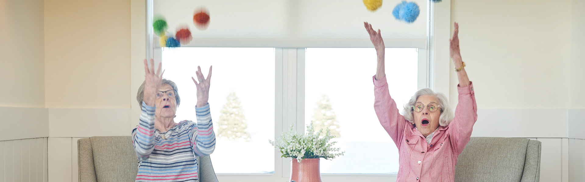 two elderly women throwing balls in the air