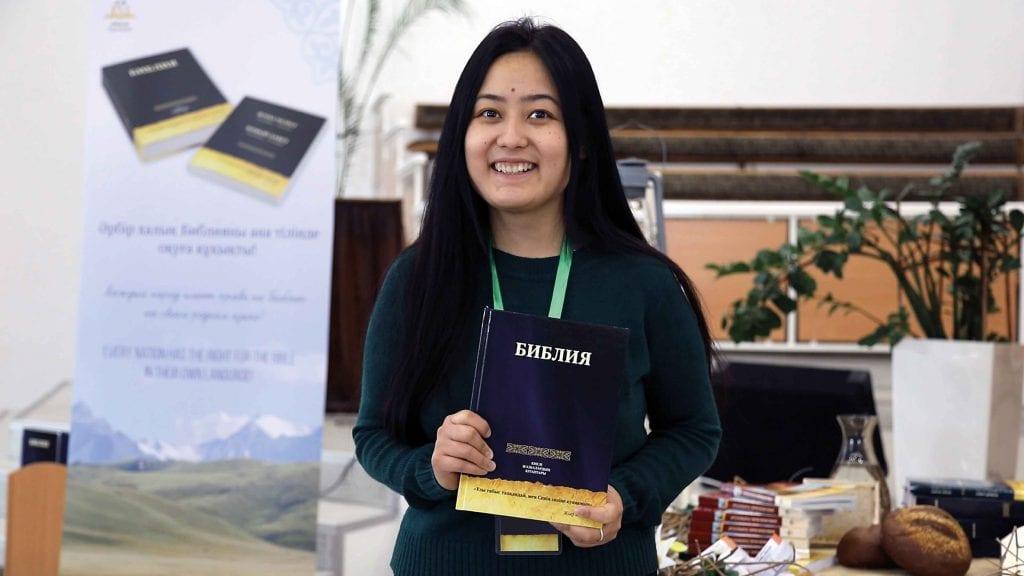 Bajan hält ihre Bibel auf kasachisch in der Hand