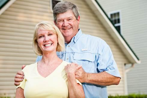 Couple in back of their home | Reverse Mortgage