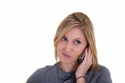 Debt Collector | Young woman listening to a telephone