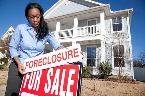 Woman putting foreclosure sign on house | Foreclosure, mortgage and charge off