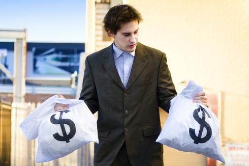 A man holding a moneybag in each hand, looking at one, wondering if to hand them over to pay a payday loan