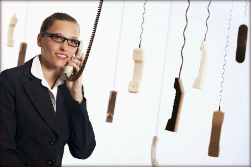 a woman picking up one phone of many hanging and reieving a call from the Midland Credit Management