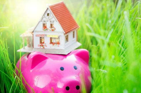 No cost mortgage refinance shown by piggy bank carrying house