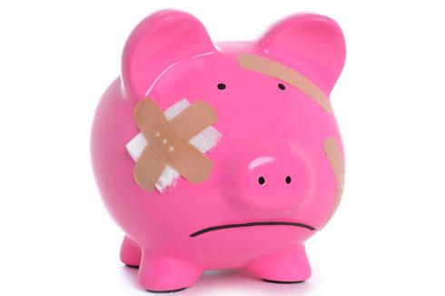 Debt. Bruised and battered piggybank.