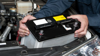 mechanic installing new battery in vehicle