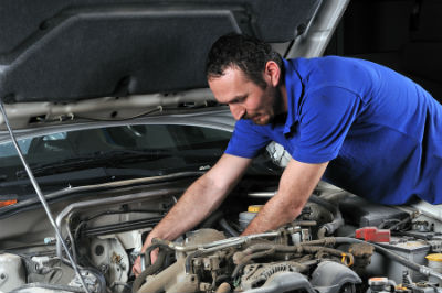 mechanic working in engine bay of vehicle