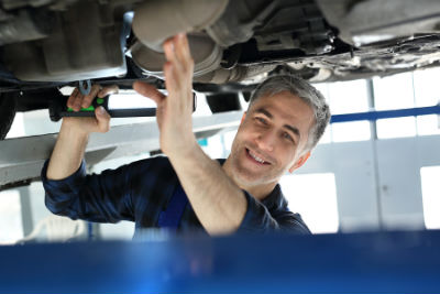 mechanic inspecting bottom of a vehicle