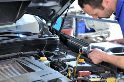 mechanic adding oil to vehicle's engine