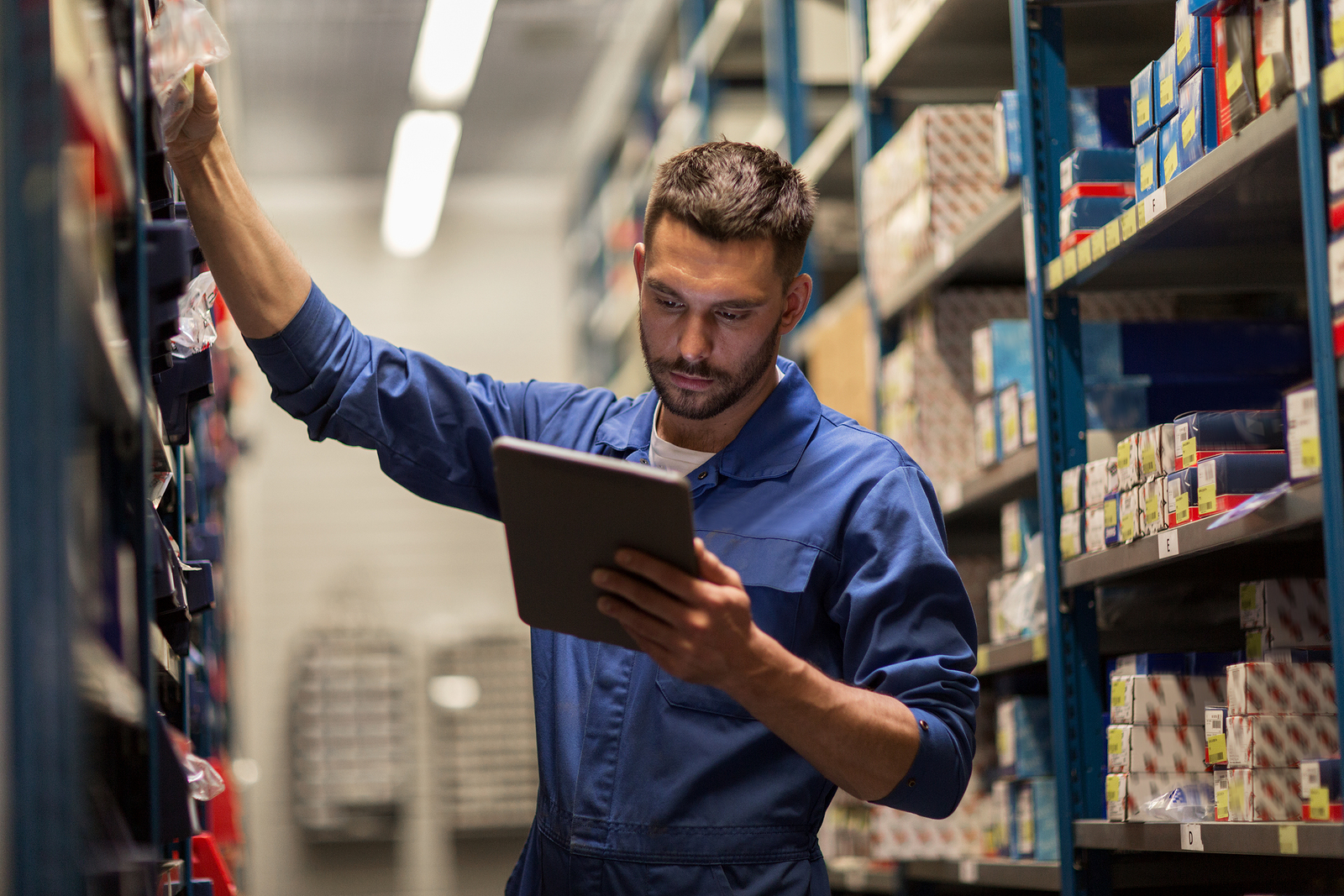 man retrieving parts from a warehouse and checking tablet