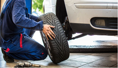 Auto technician replacing tire