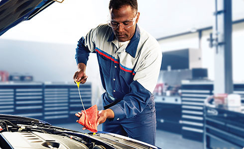 Ford service technician performs oil change