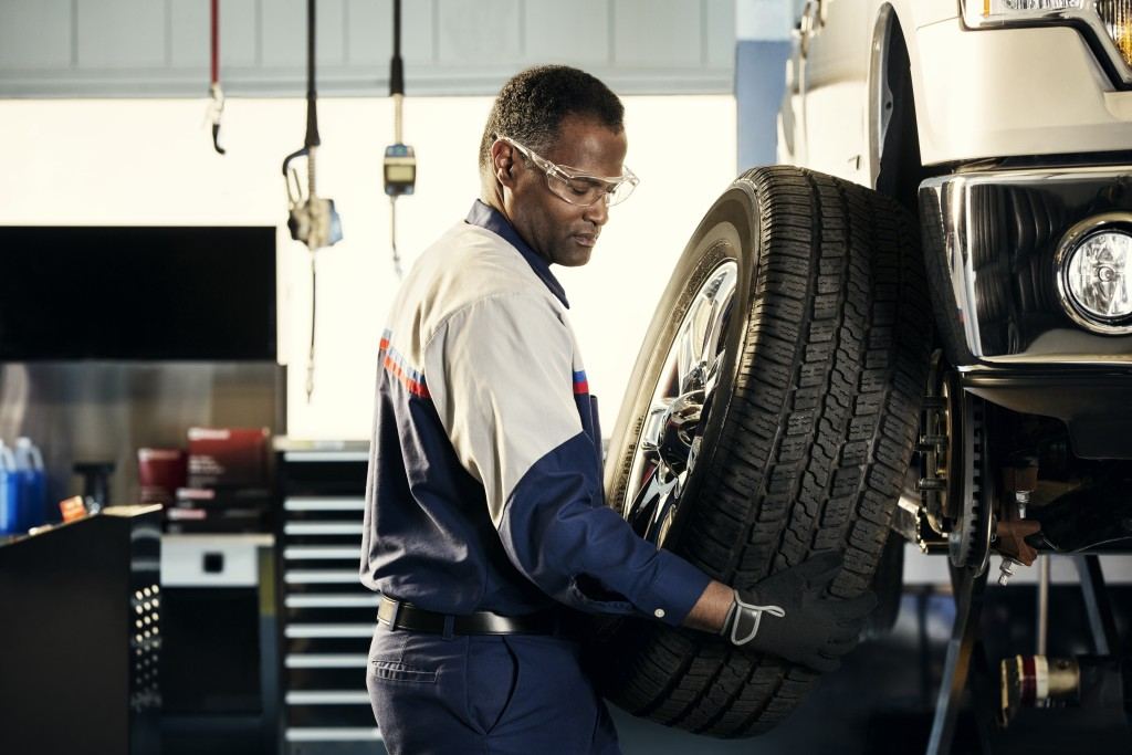 Certified Ford technician performing a tire rotation
