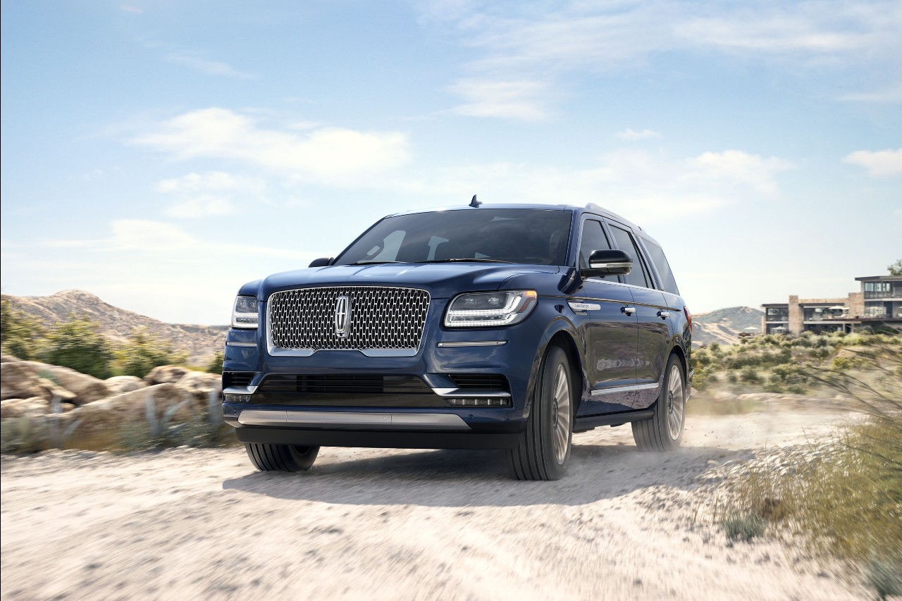 Blue 2019 Lincoln Navigator driving through dirt and sand