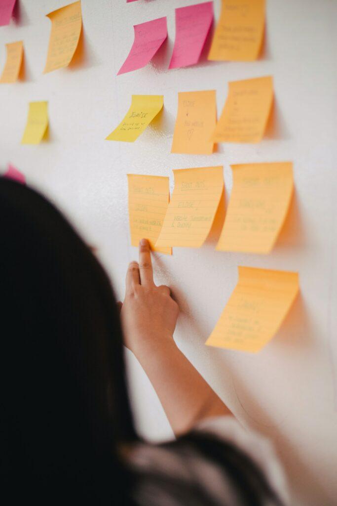 Mujer pegando papeles de colores en la pared para hacer un mapa conceptual sobre los guest posts.