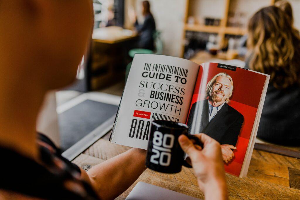 un hombre con una entrevista en una mano y una tasa en la otra en lo que parece ser un open office