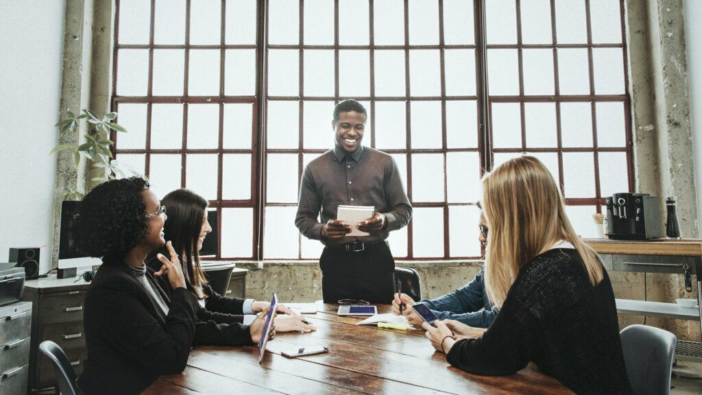 Cuatro compañeros de trabajo en una oficina, representando a varias personas hablando sobre los beneficios del marketing digital.