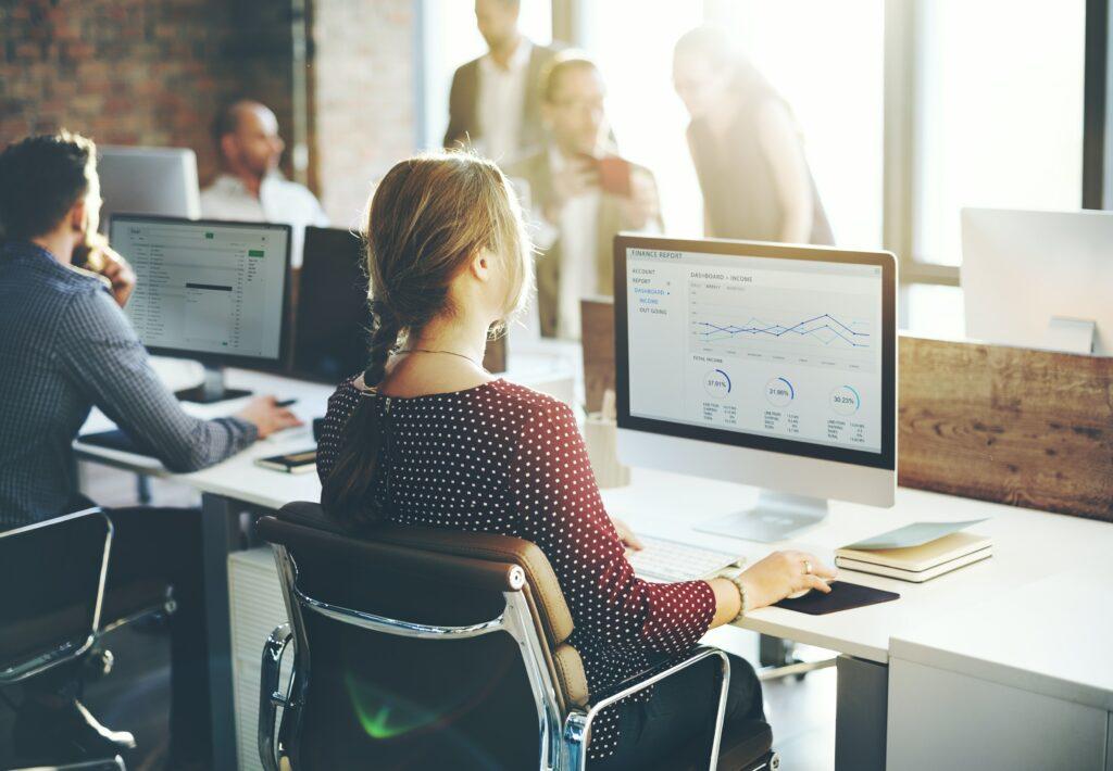 Mujer utilizando un computador, representando a una mujer buscando información sobre marketing digital.
